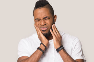 Man struggles with the effects of impacted teeth